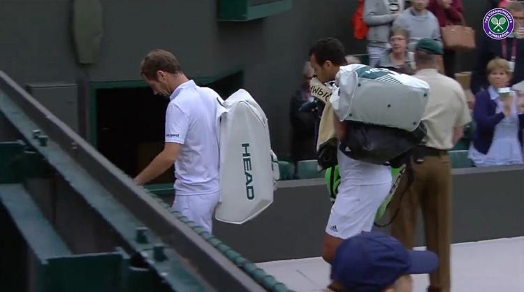 Jo-Wilfried Tsonga porte un des sacs de Richard Gasquet en sortant du court.