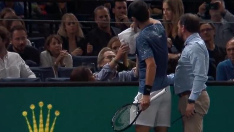 Novak Djokovic donne une serviette humide à un spectateur au bord du malaise au Rolex Paris Masters 2018.