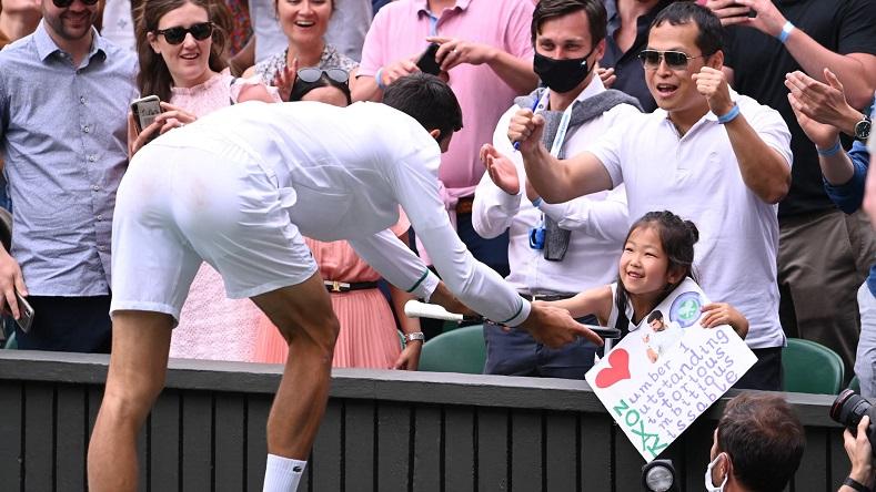 Novak Djokovic donne sa raquette à une petite fille après avoir gagné son 20e titre du Grand Chelem à Wimbledon 2021.
