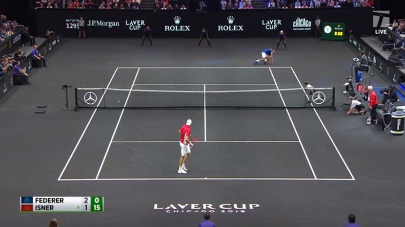 John Isner contraint Roger Federer à mettre une main à terre sur un service au corps surpuissant lors de la Laver Cup 2018.