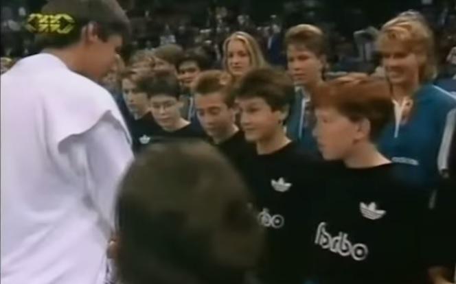 Vainqueur du tournoi de Bâle 1993, Michael Stich remet une médaille à un ramasseur de balles au nom de Roger Federer.